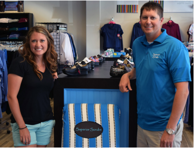 Man and woman standing in store; scrubs hanging on clothes ranks behind them