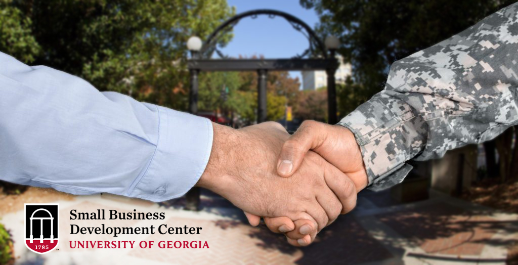 Civilian and soldier shake hands in front of the arch, SBDC logo in corner